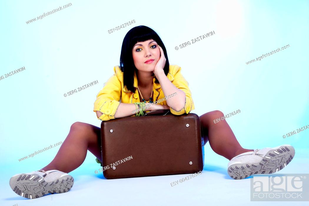 Stock Photo: brunette with suitcase sitting.