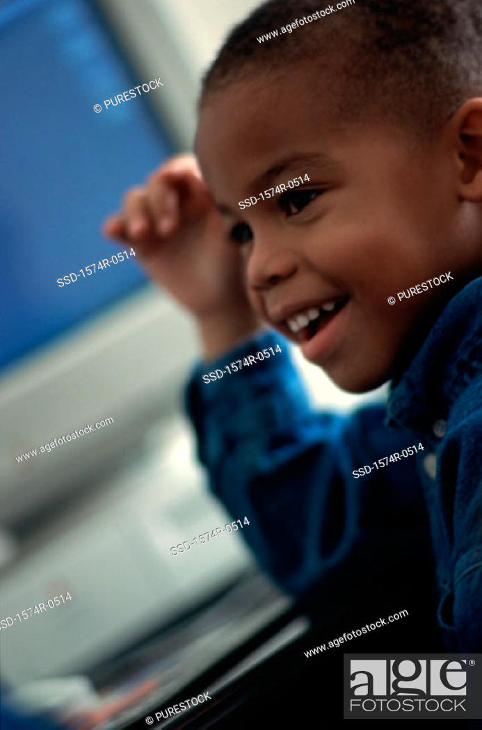 Stock Photo: Boy sitting in front of a computer.