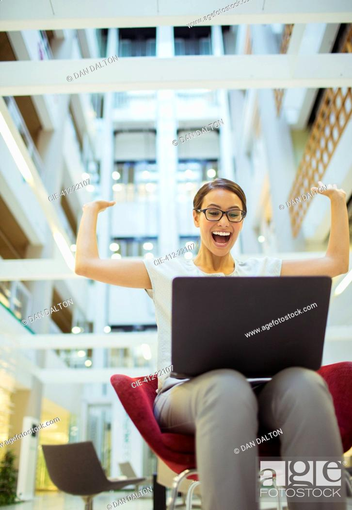 Stock Photo: Businesswoman getting excited in office building.
