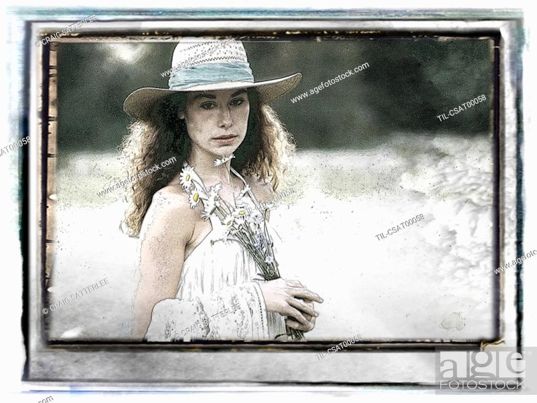 Stock Photo: A young woman wearing a straw hat holding daisies.