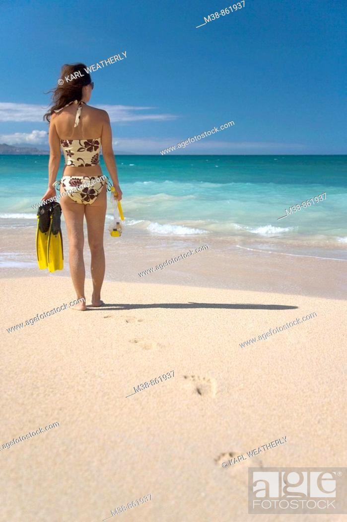 Stock Photo: Woman holding snorkel gear on the beach  Maui, Hawaii.