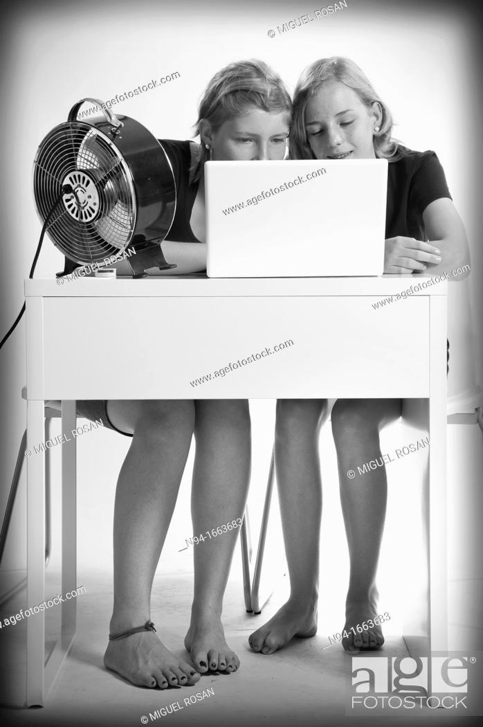 Stock Photo: Two teenage girls studying Central European and laptop front.