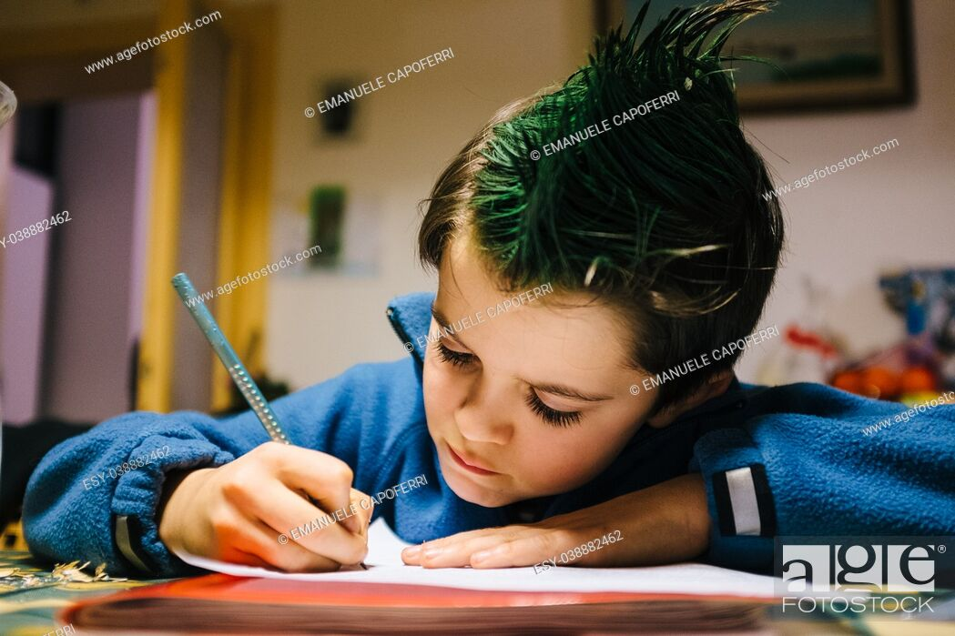 Stock Photo: portrait of 9 year old boy at home with green colored hair crest performing school homework.