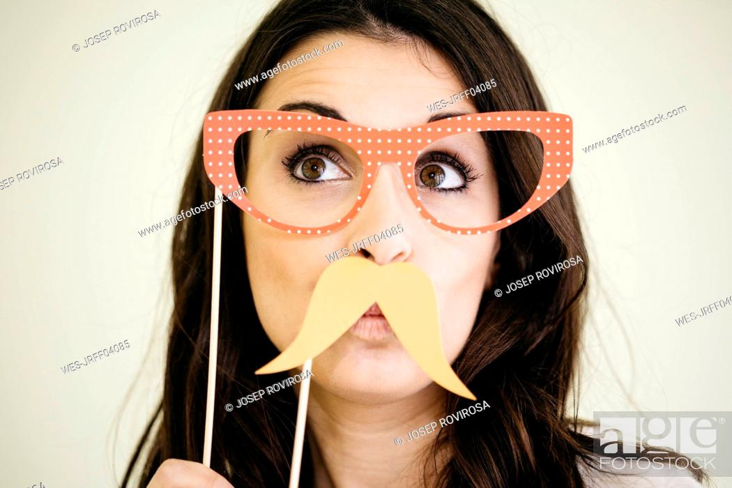 Stock Photo: Portrait of young woman with comedy glasses and fake moustache.