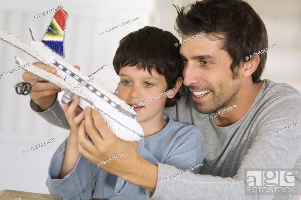 Stock Photo: Father and son playing with model aeroplane.