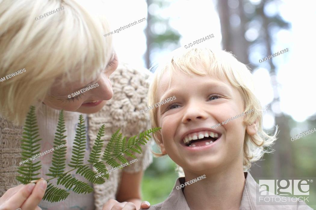 Stock Photo: Mother tickling son with fern leaf.