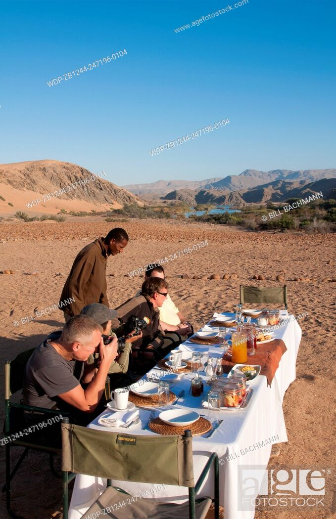 Imagen: Namibia Africa Northern Desert of Namib Desert border of Angola and Kunene River safari with lunch on river with tent and campers in Hartmann Berge deserted.