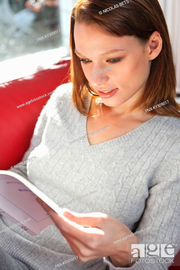Stock Photo: Young woman reading a book.