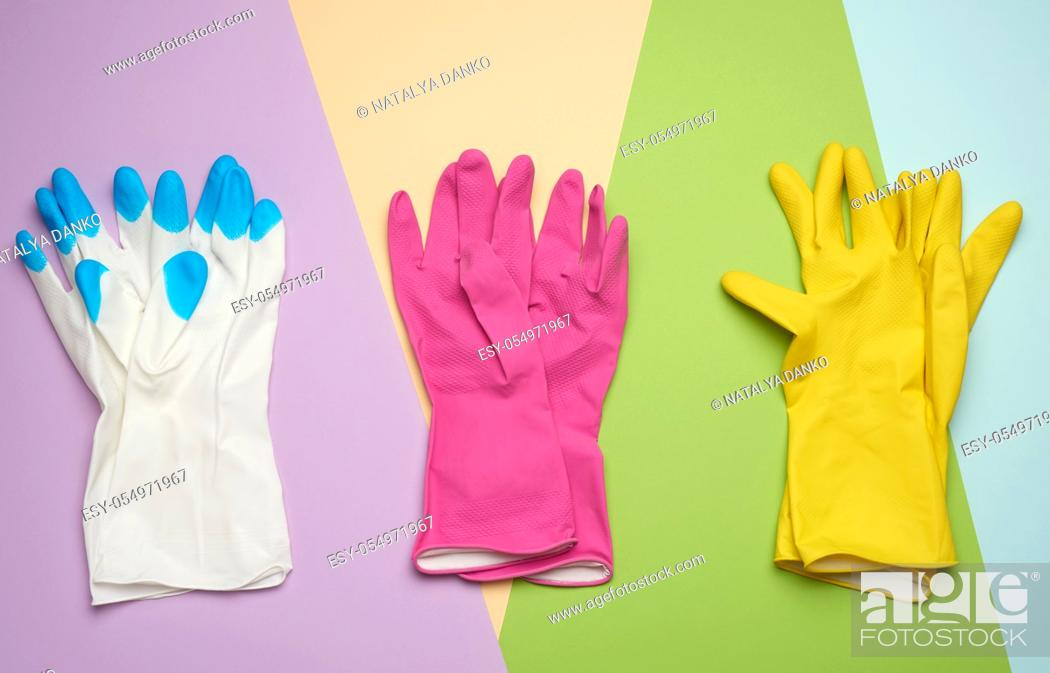 Stock Photo: three pairs of protective rubber gloves on a colored background, top view, flat lay.