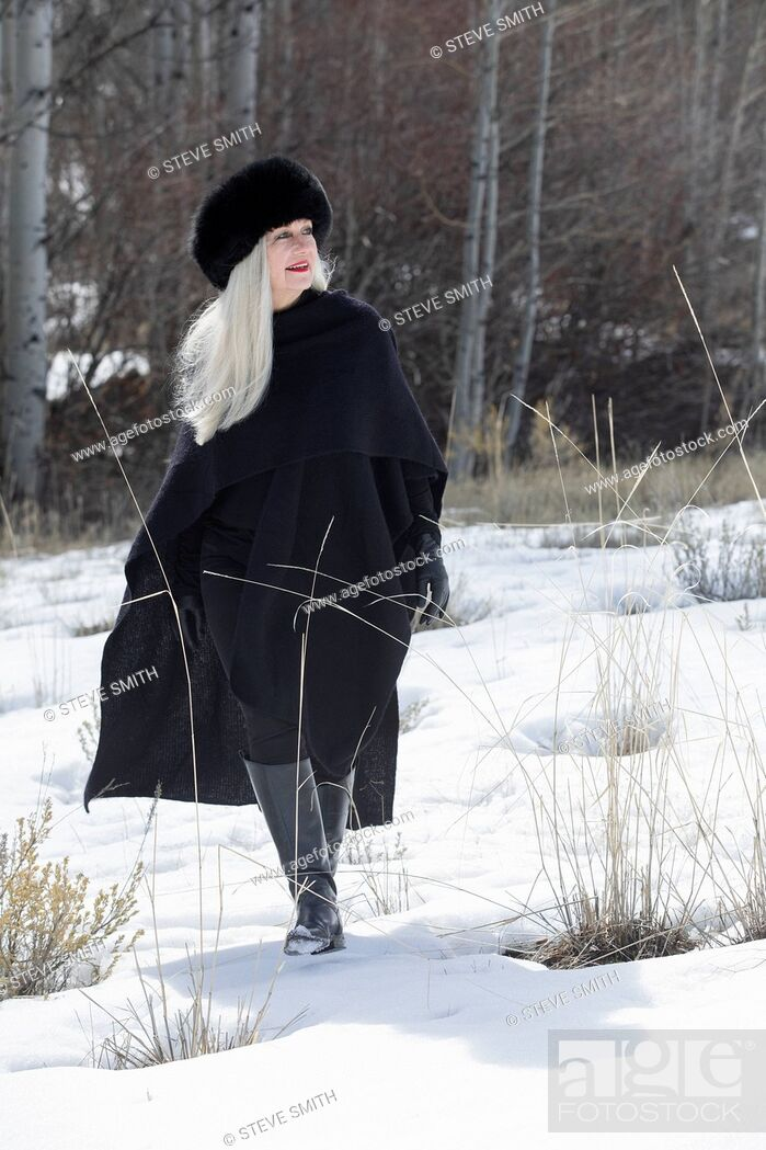 Stock Photo: Woman with ushanka walking in snow.
