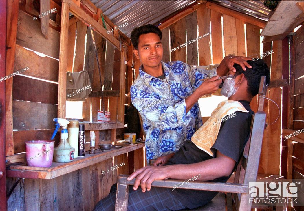 Stock Photo: Indian barber shaving a young man with a razor, India, Uttar Pradesh, Varanasi.