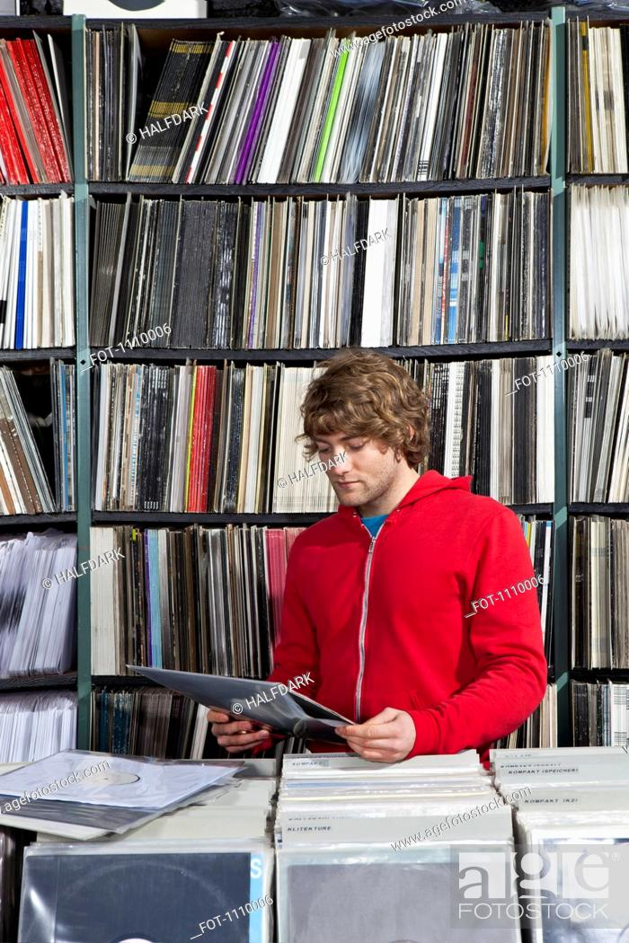 Stock Photo: A young man considering a record at a record store.