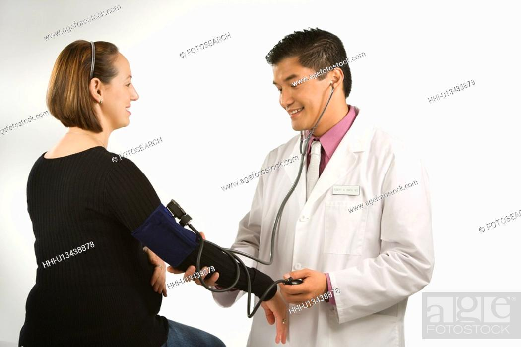 Stock Photo: Asian American male doctor testing blood pressure of pregnant Caucasian woman.