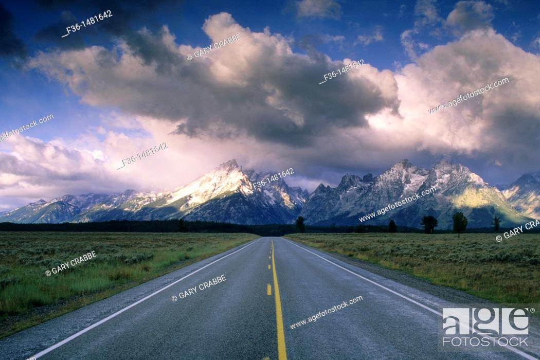 Stock Photo: Straight road below mountain range dusted by first snow of fall, Grand Teton National Park, WYOMING.