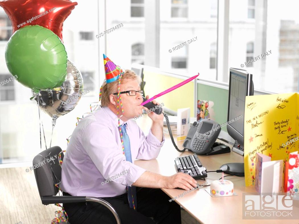 Stock Photo: Businessman having birthday party at desk.