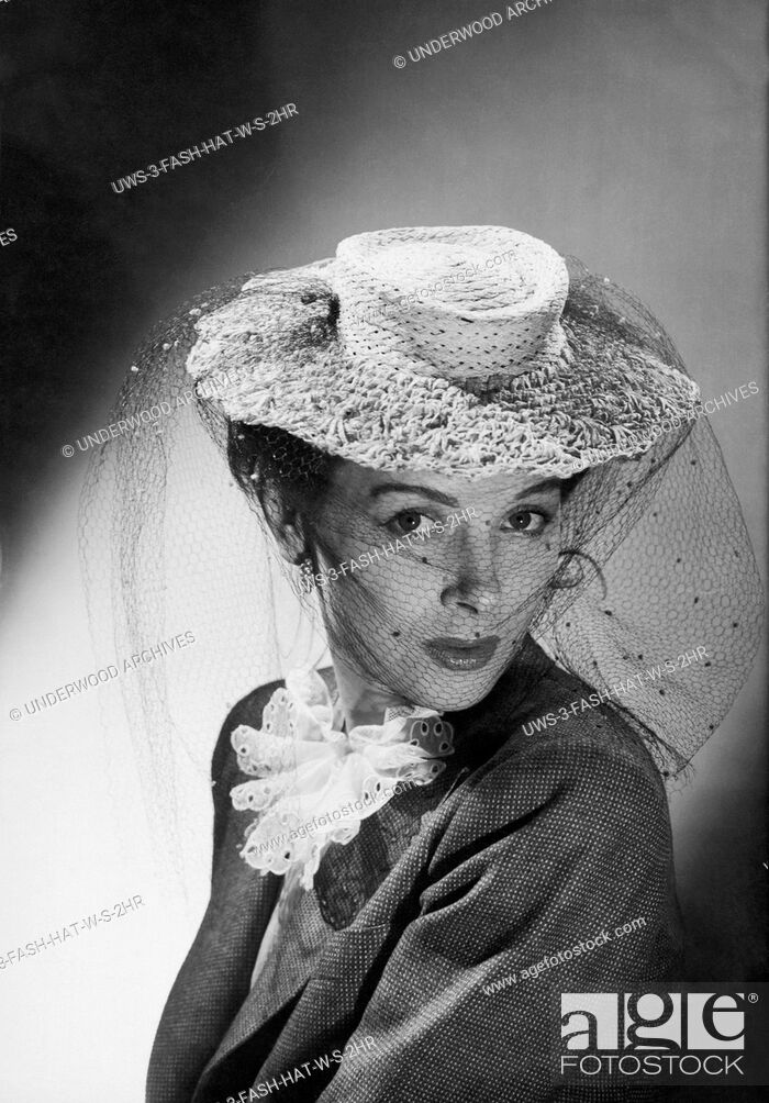 Stock Photo: United States: c. 1948 A fashion photo of a woman wearing a hat with a veil.