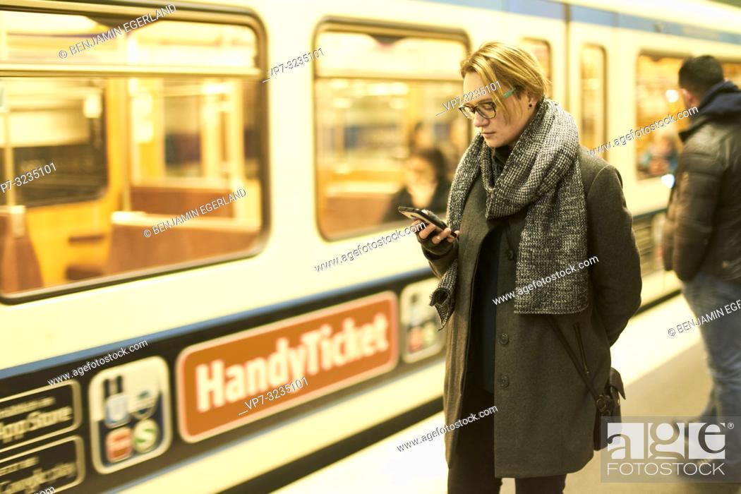 Stock Photo: woman using smartphone in subway, Munich, Germany.