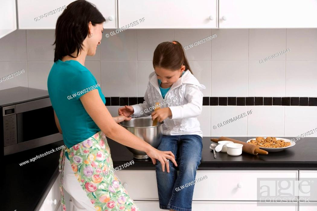 Stock Photo: Side profile of a young woman preparing food with her daughter in the kitchen.