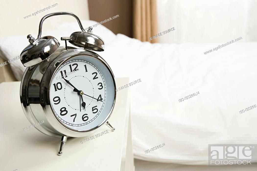 Stock Photo: Alarm clock by bed.