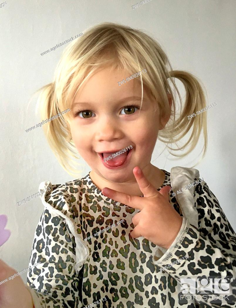 Stock Photo: Portrait on a little blond girl who sticking out the tongue, 2 1/2 years old, in Ystad, Scania, Sweden.
