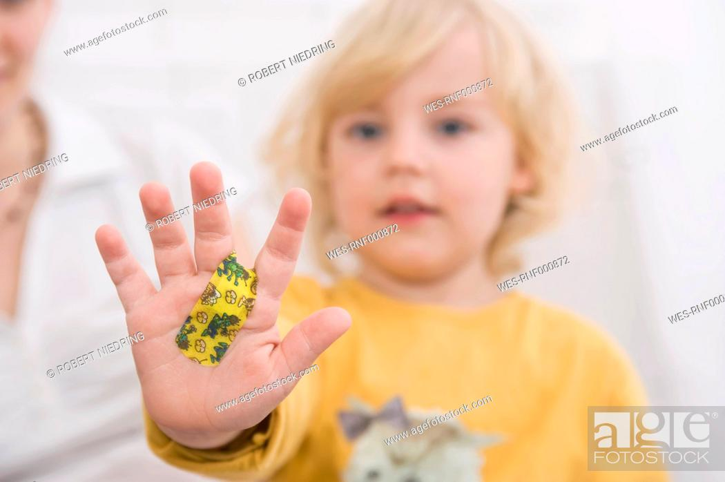 Stock Photo: Daughter showing hand with bandage, close up.