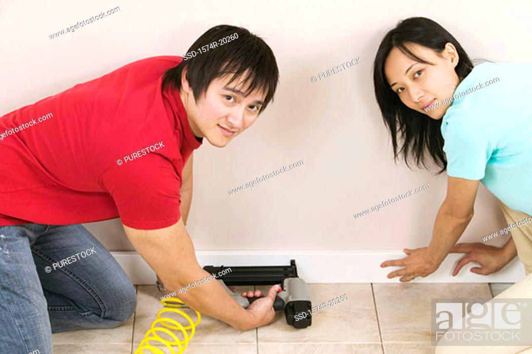 Stock Photo: Portrait of a young man using a drill on a wall with a young woman helping him.