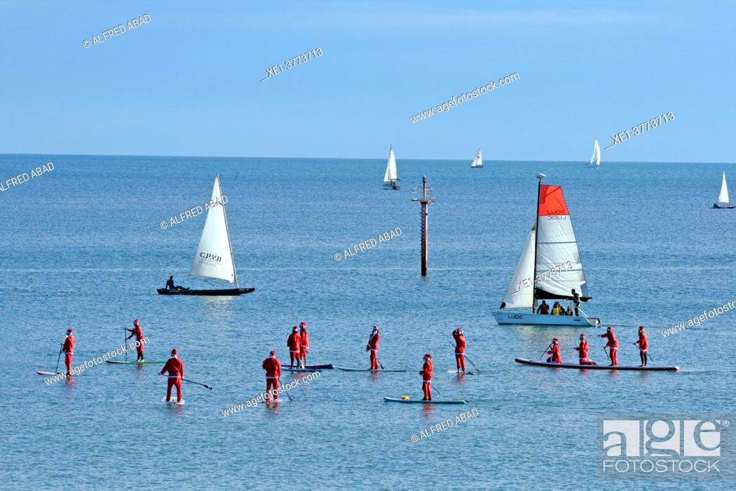 Stock Photo: Santa Claus in paddle surf and sail boats in front of the beaches of Barcelona, Catalonia, Spain.