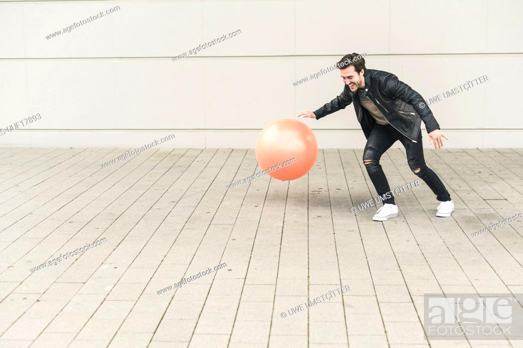 Stock Photo: Young man in leather jacket, playing with a gym ball.