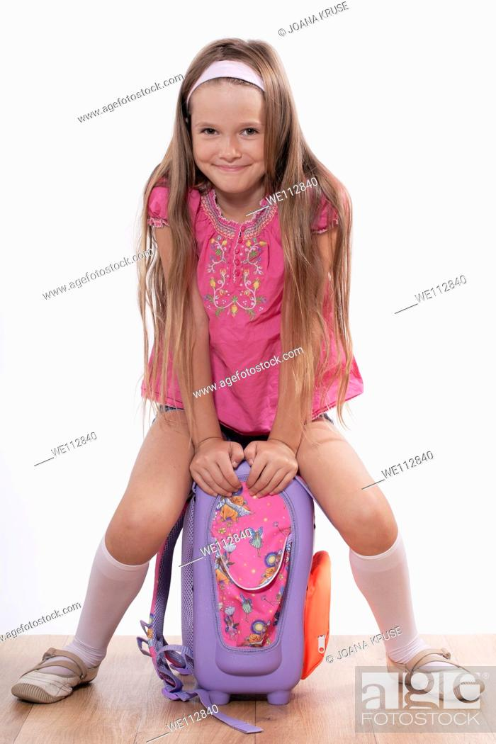 Stock Photo: eight year old girl sitting with a satchel on the floor.