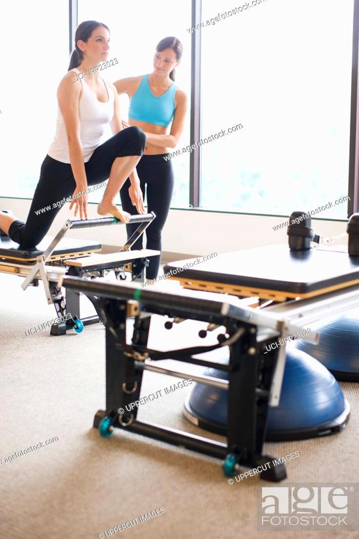 Stock Photo: Native American personal trainer guiding woman on pilates equipment.