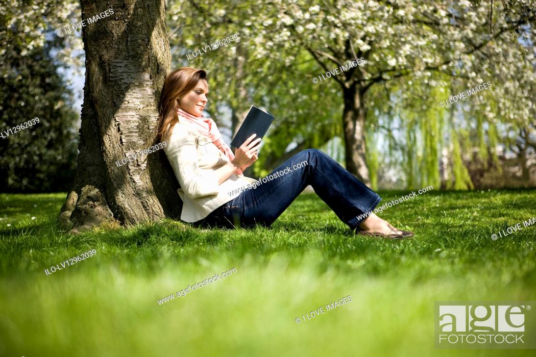 Stock Photo: A young woman leaning against a tree, reading a book.