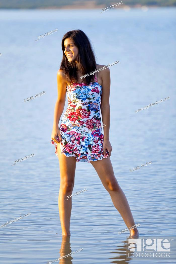 Stock Photo: Attractive young woman hiking up her Summer dress exposing her thigh.