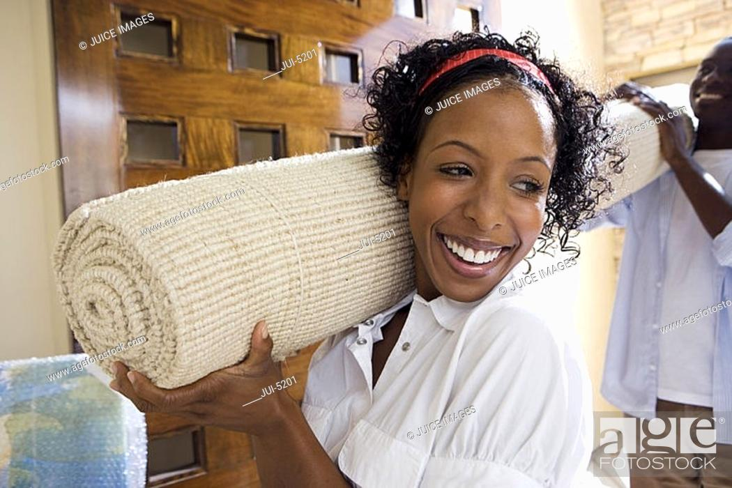 Stock Photo: Couple moving house, carrying rolled-up carpet on shoulders through doorway, smiling.
