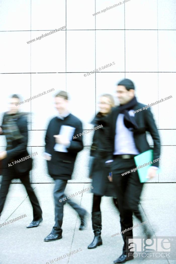 Stock Photo: Business associates walking together down sidewalk.