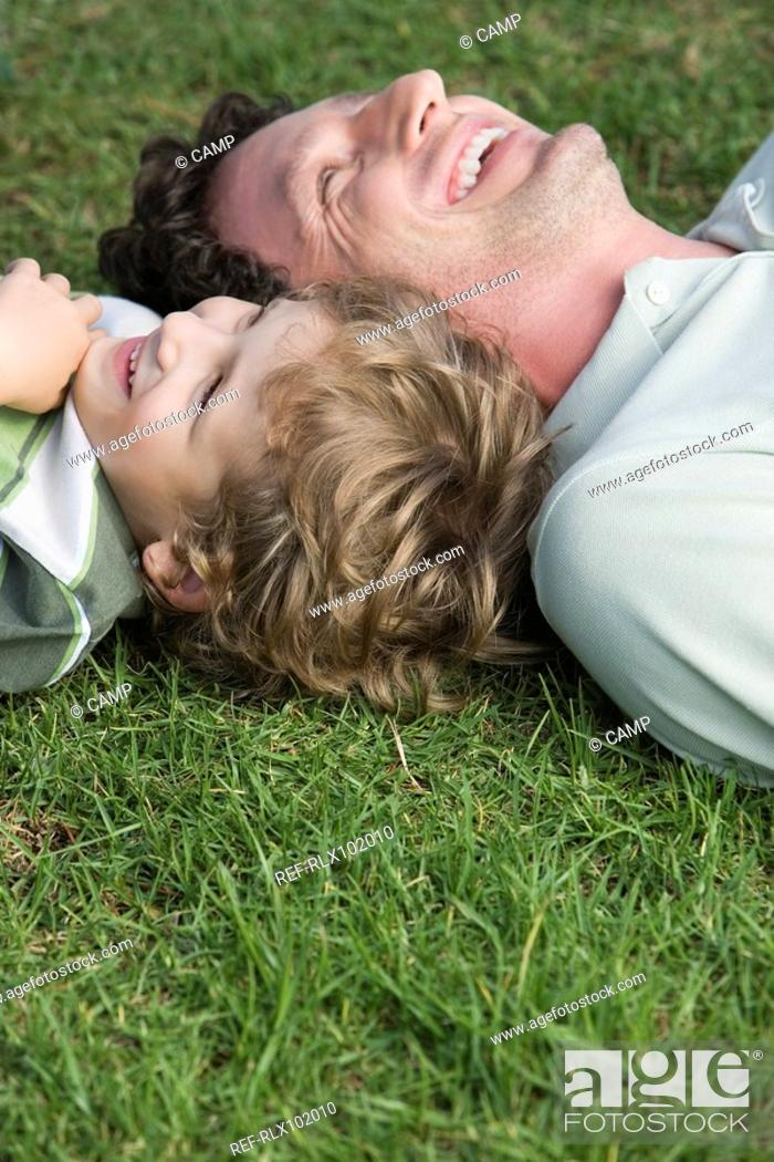 Stock Photo: Father and son 4-7 lying on grass, looking up, laughing.