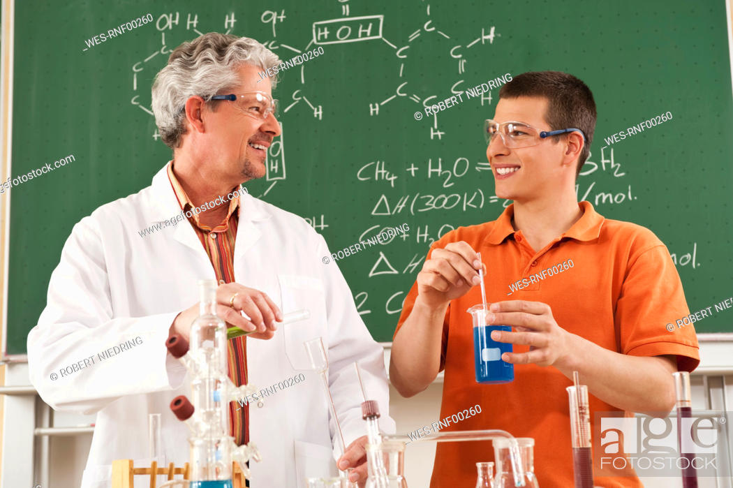 Stock Photo: Germany, Emmering, Teacher and student doing experiment in chemistry class, smiling.