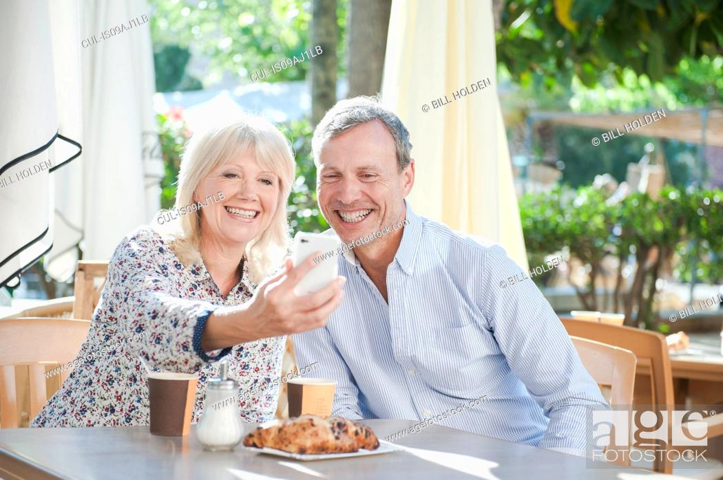 Stock Photo: Couple taking selfie with smartphone at cafe.