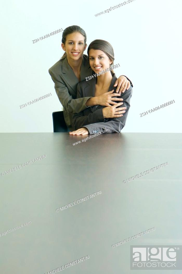 Stock Photo: Teenage twin sisters dressed in suits, embracing, smiling at camera together, portrait.