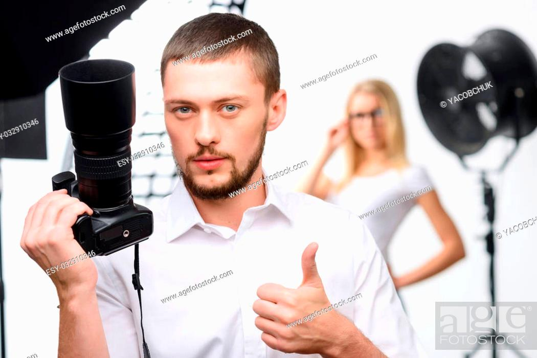 Stock Photo: Good work. Nice-looking young male photographer holds up a camera while showing thumbs up.