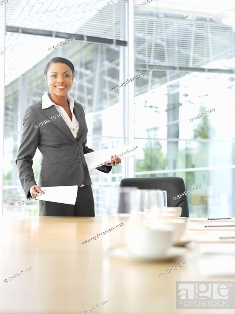 Stock Photo: Businesswoman with paperwork in conference room.
