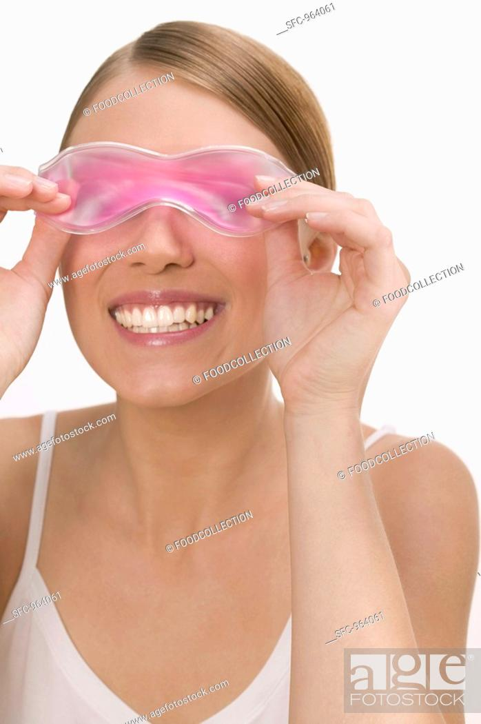 Stock Photo: Woman with a cooling eye mask.