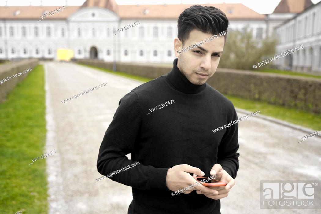 Stock Photo: young man with phone in front of aristocratic Nymphenburg Palace, touristic sight, in Munich, Germany.