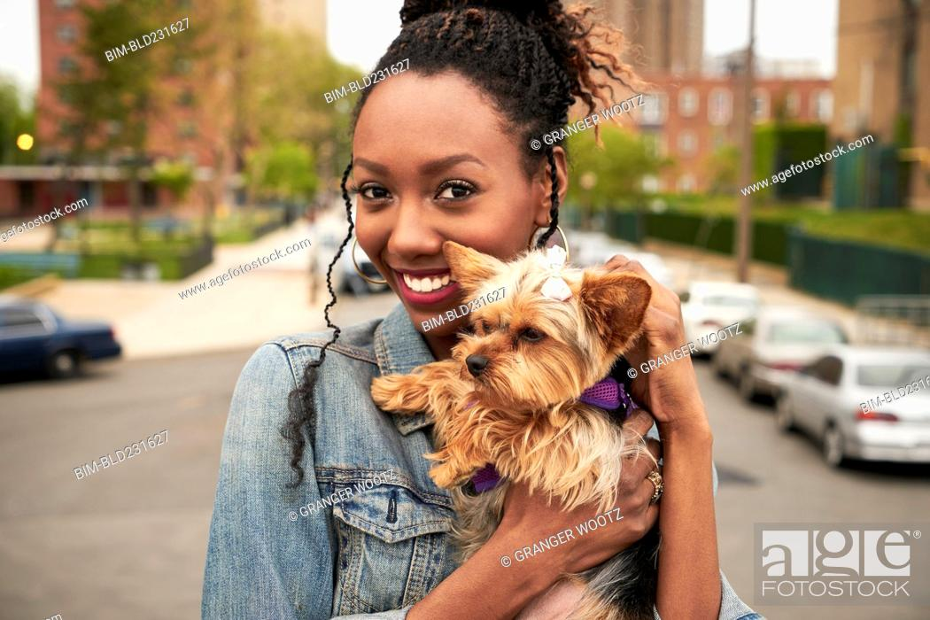 Stock Photo: Black woman holding dog in city.