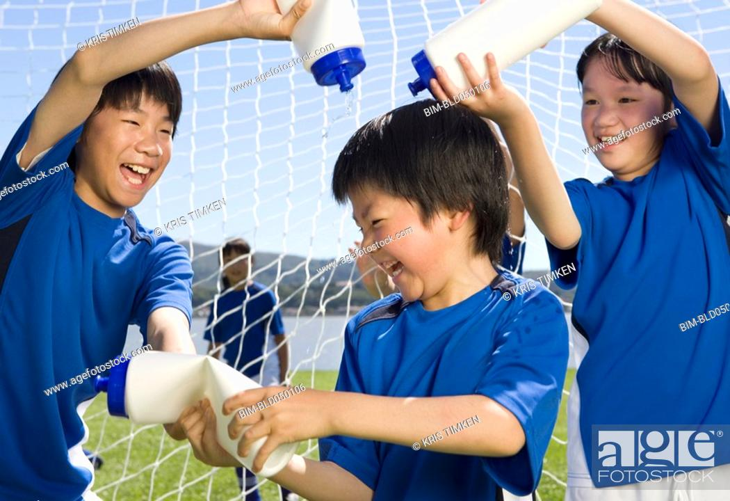 Stock Photo: Asian boys playing with water bottles.