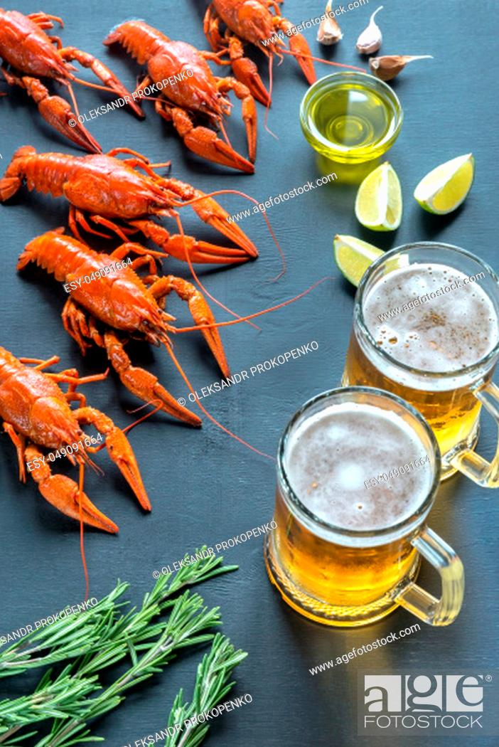 Stock Photo: Boiled crayfish with two mugs of beer.