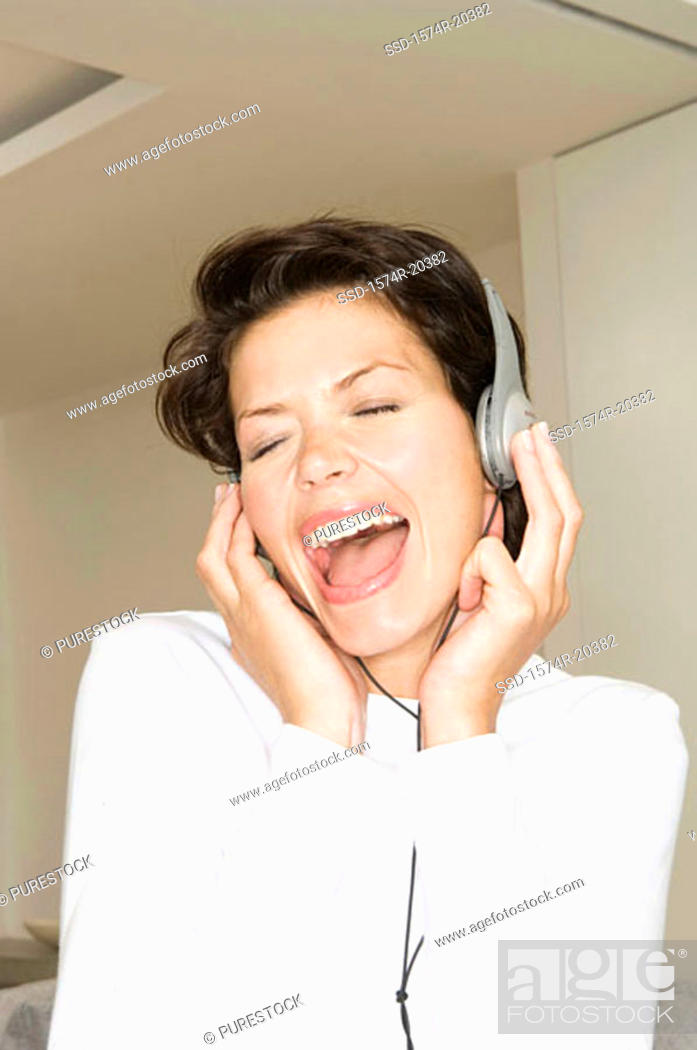 Stock Photo: Close-up of a young woman wearing headphones and listening to music.