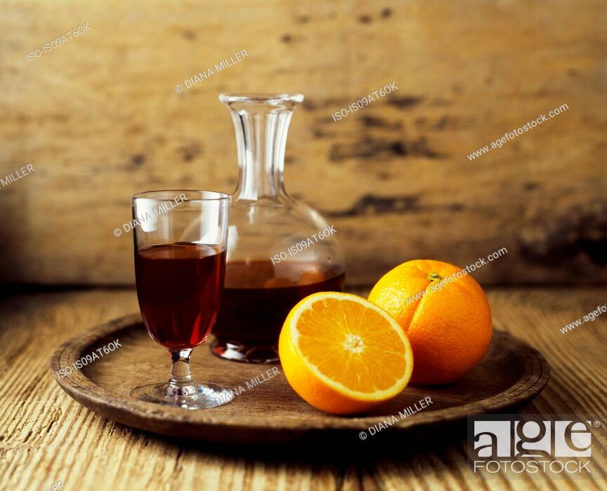 Stock Photo: Still life of red wine decanter and fresh orange fruit.