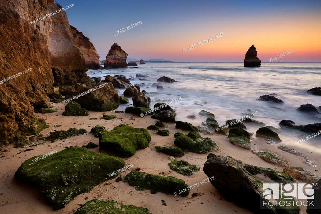 Stock Photo: Sunrise at Algarve rocky coast near Lagos, Algarve, Portugal.