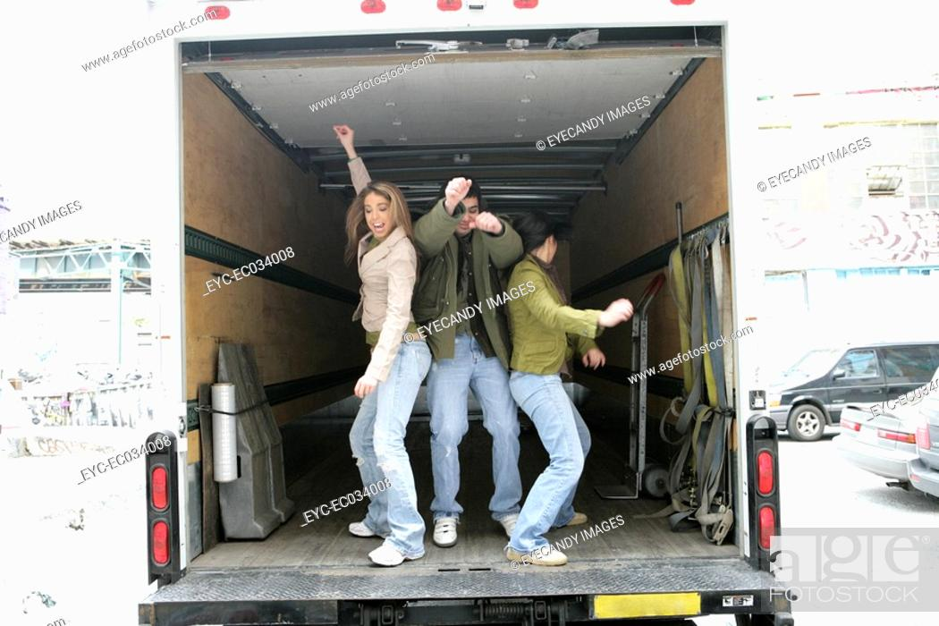 Stock Photo: View of three people dancing in a van.