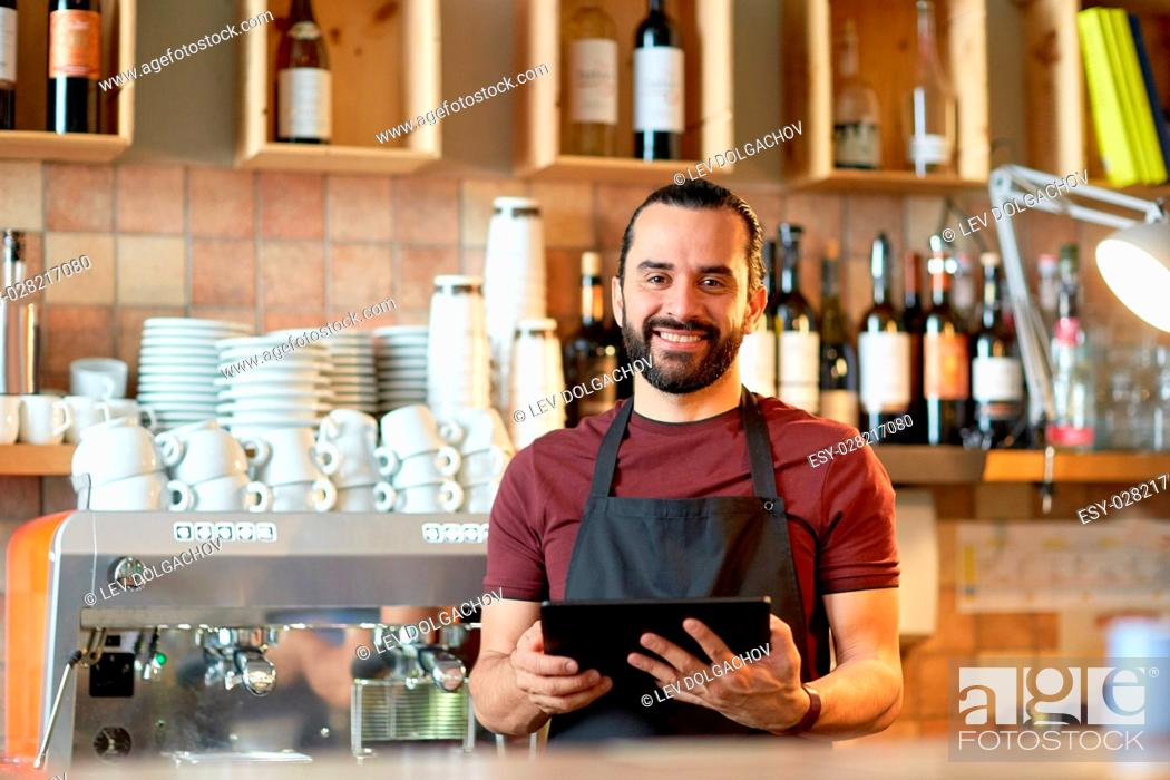 Stock Photo: small business, people, technology and service concept - happy man or waiter in apron with tablet pc computer at bar or coffee shop.